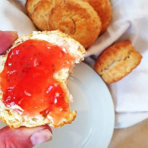 A scone covered in strawberry jam with a bite taken from it.