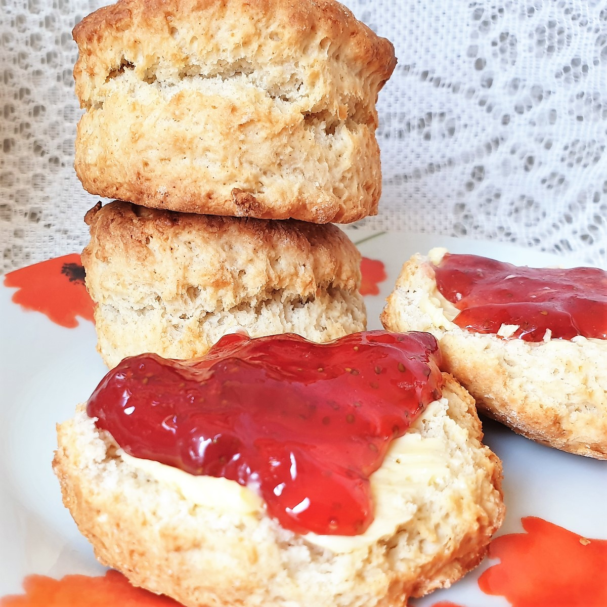 A scone covered in strawberry jam in front of a pile of scones.