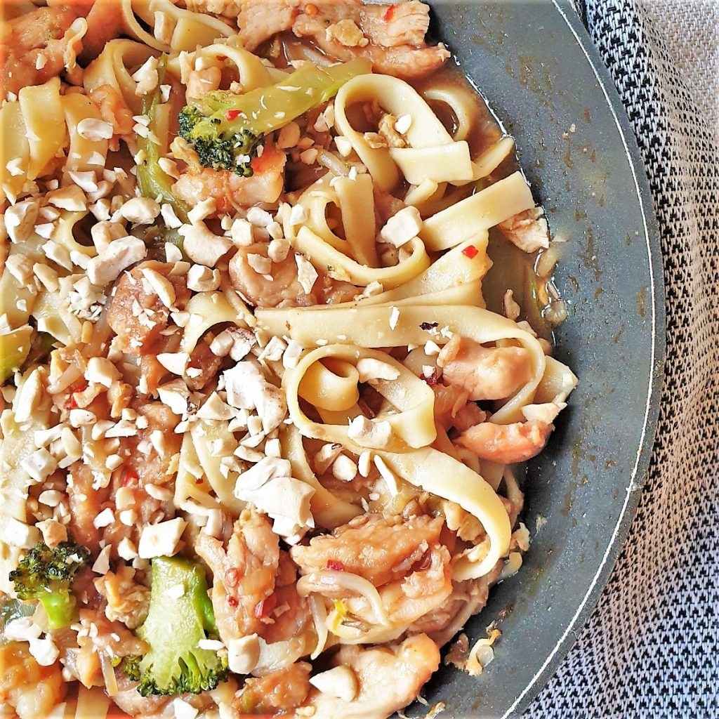 A pan of chicken and shrip pad thai noodles garnished with peanuts.