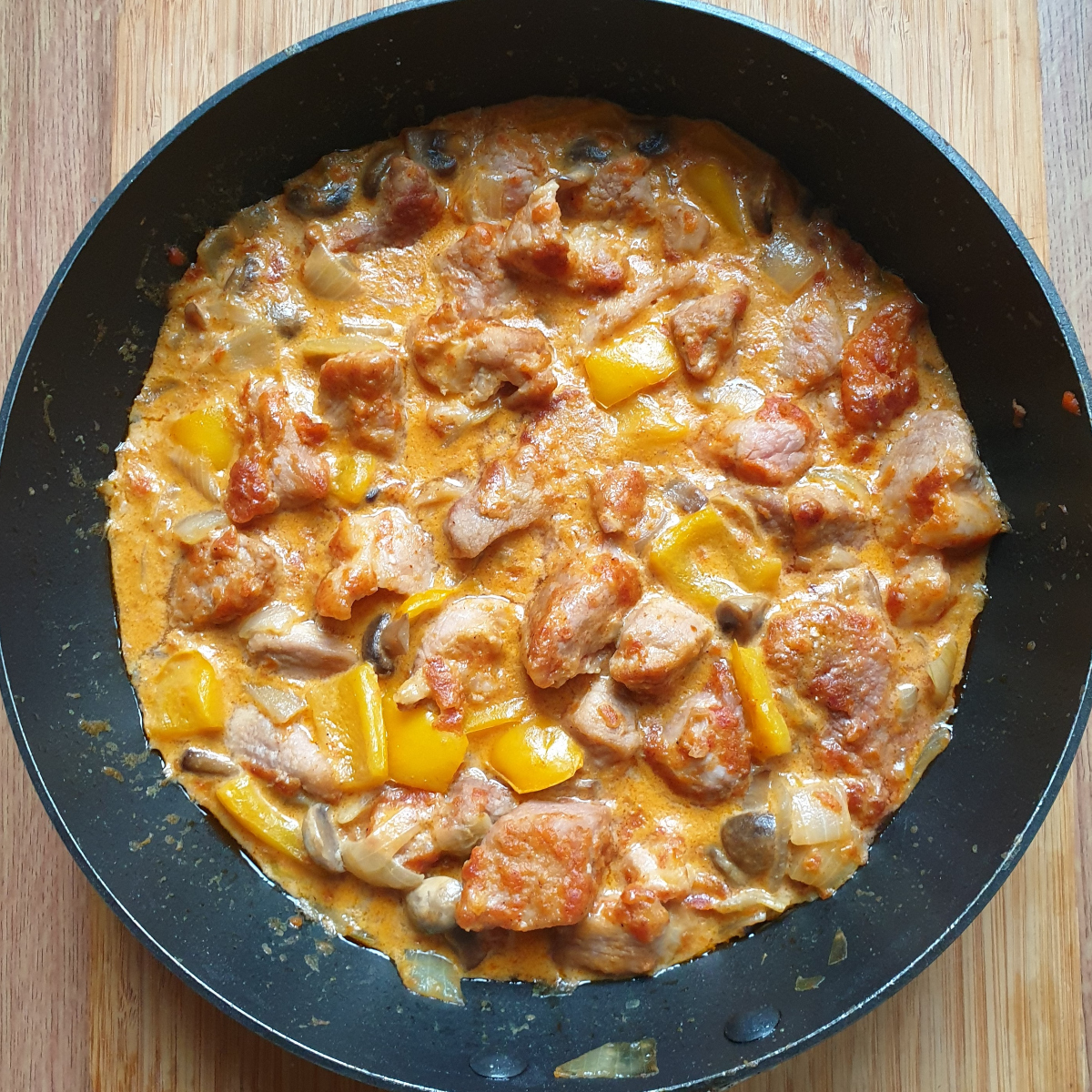 A pan of pork pieces in paprika sauce.