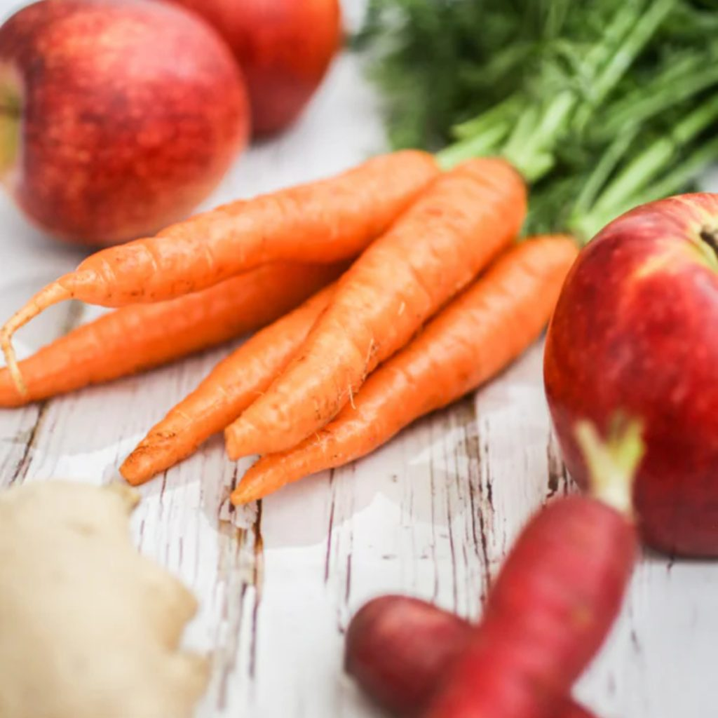 A bunch of fresh carrots with apples.