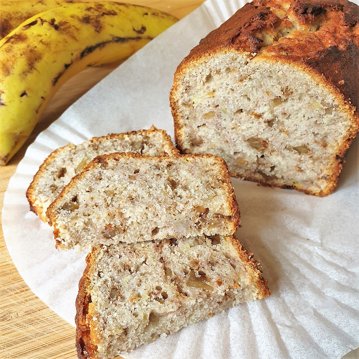 Slices of banana walnut bread in front of the whole loaf, next to a banana.