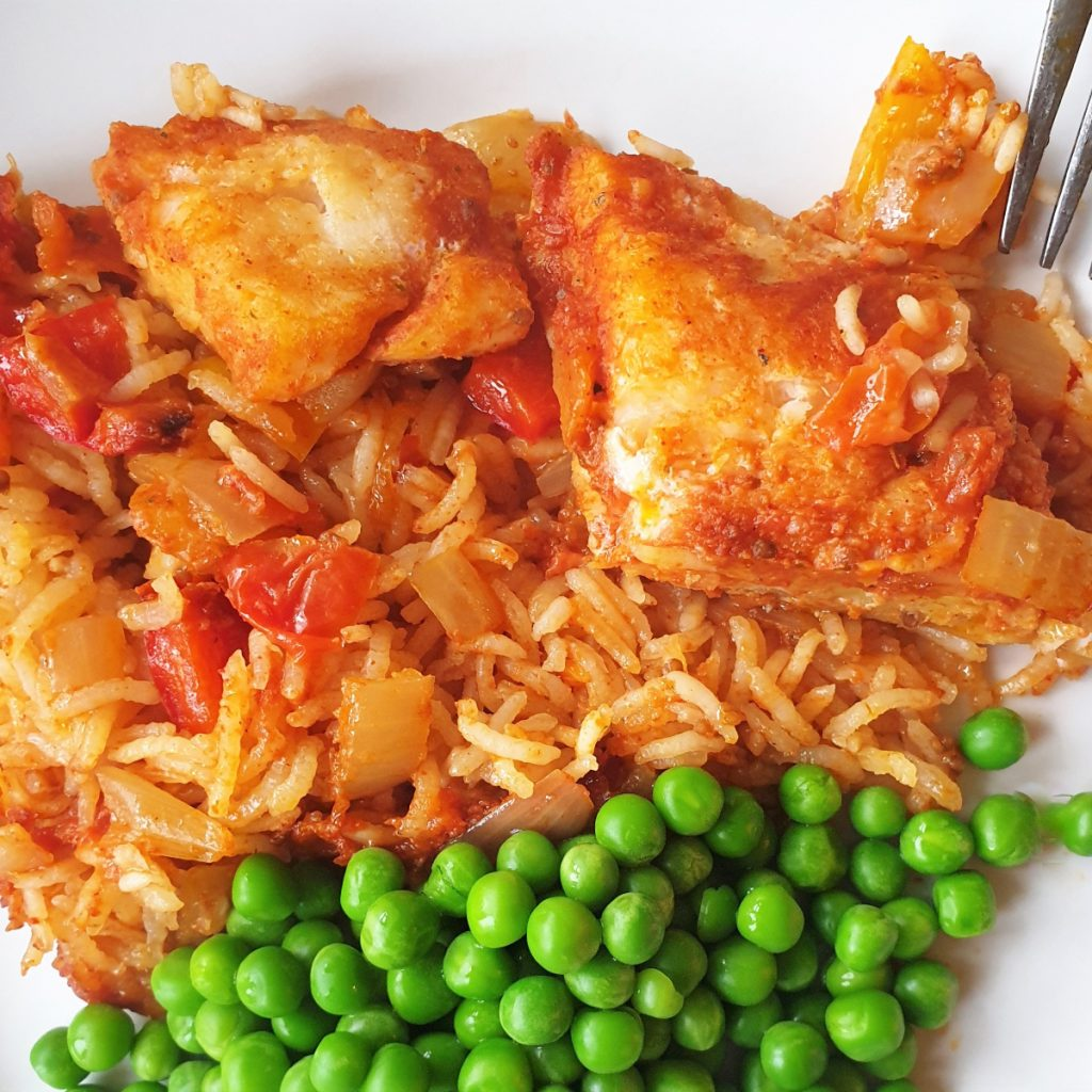 A plate of spicy fish and rice with peas.