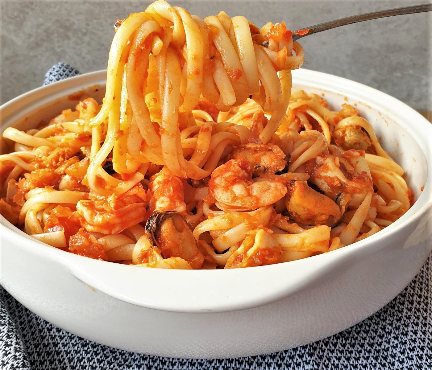 A forkful of linguine over a bowl of pasta pescatone.