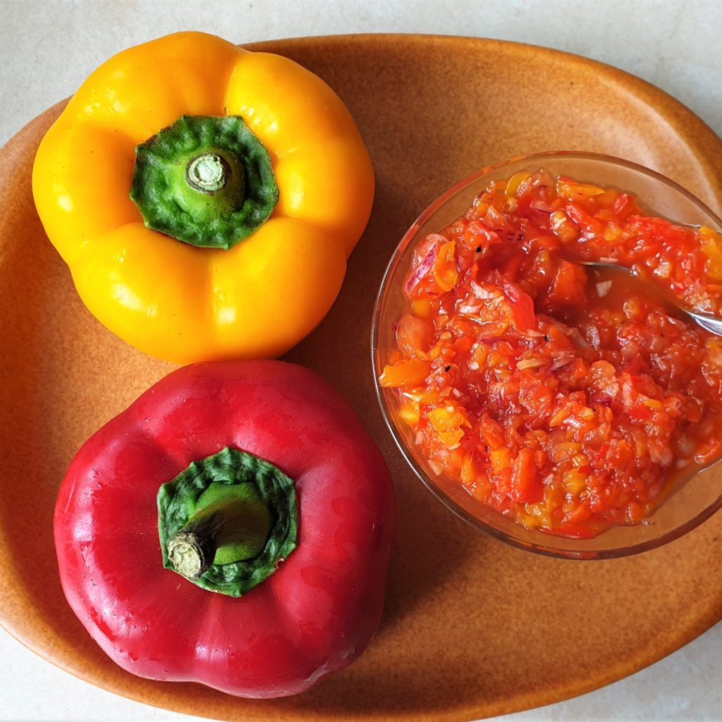 A red pepper and yellow pepper along side a dish of sweet pepper relish.