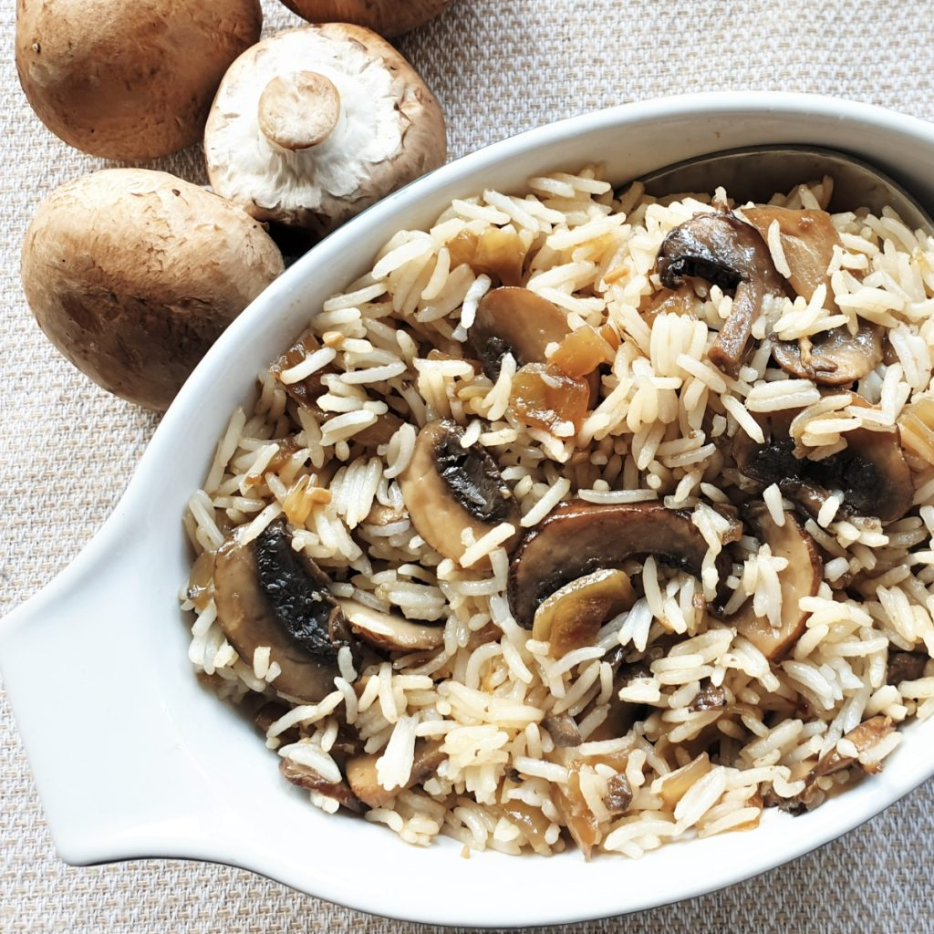 A dish of mushrom fried rice next to raw mushrooms.
