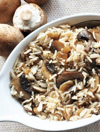A dish of mushrom fried rice next to raw mushrooms.
