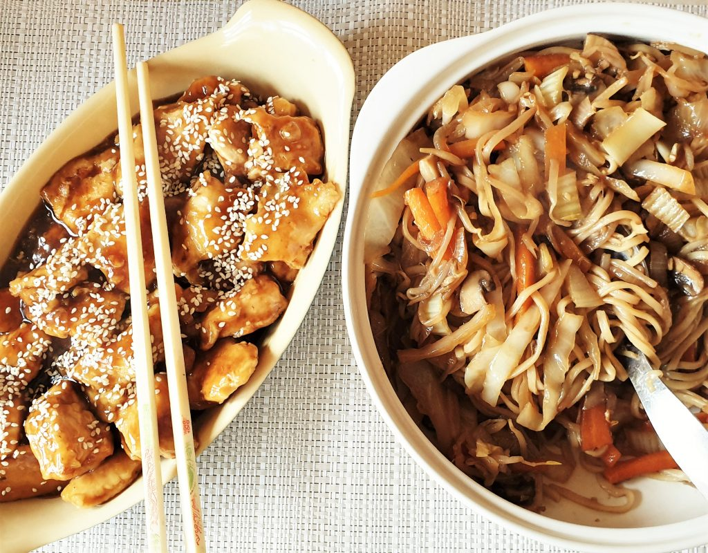 Sesame chicken with a bowl of chow mein.
