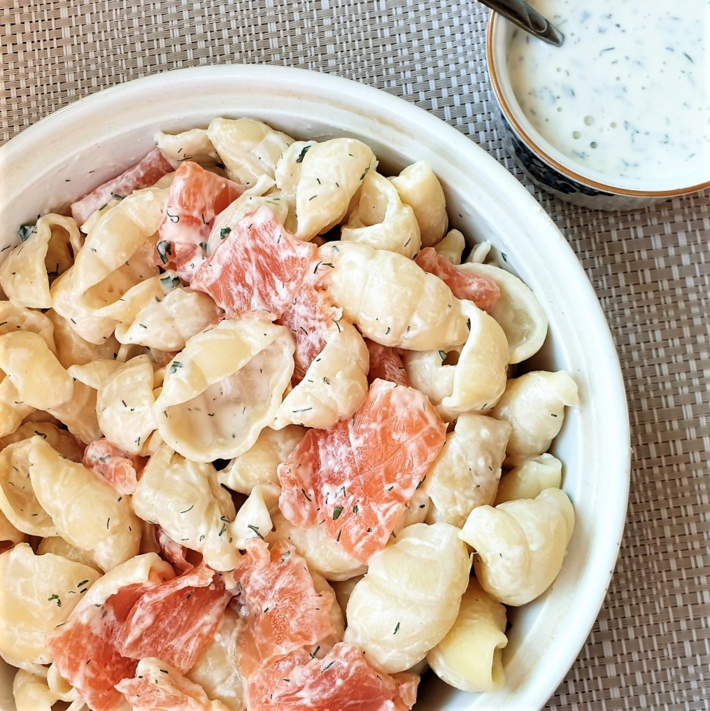 A bowl of smoked salmon pasta salad with a dish of homemade ranch dressing.