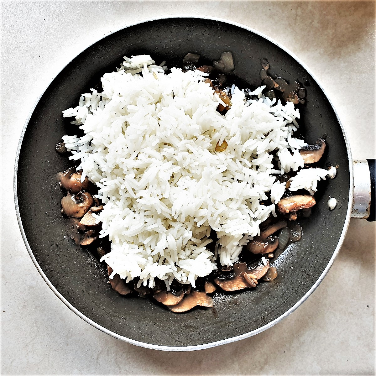 Rice being added to fried mushrooms and onions.