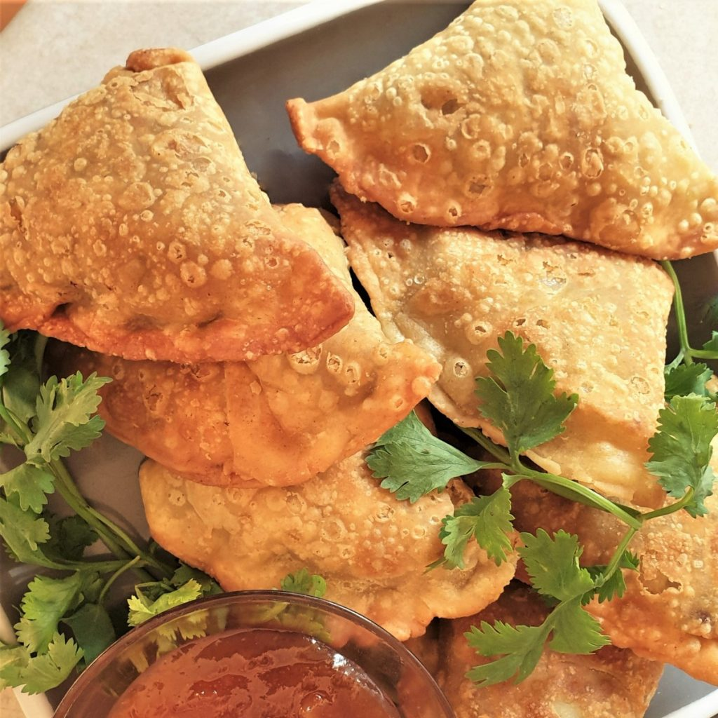 A plate of fried beef samosas.
