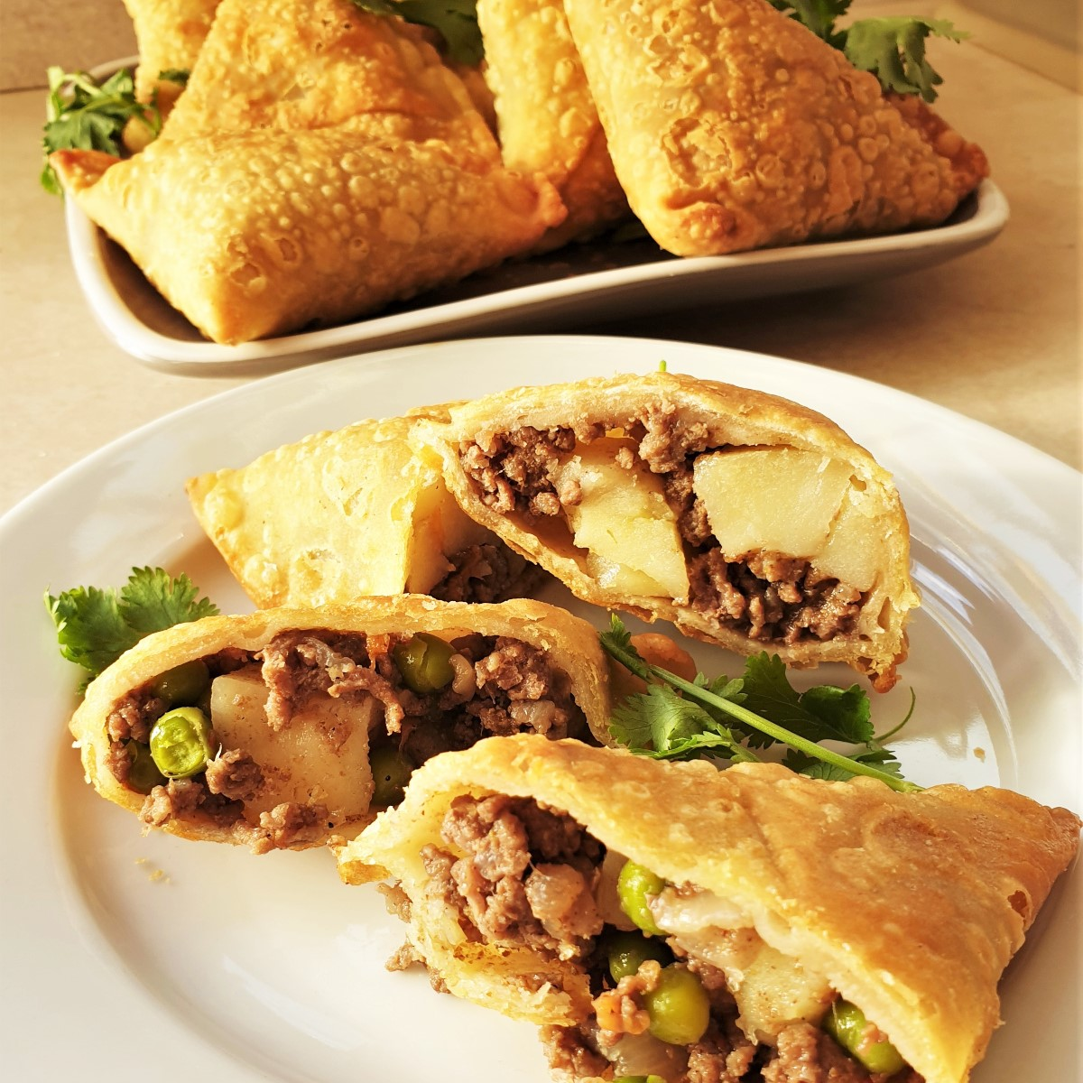 Two beef samosas cut open on a plate, showing the inside.