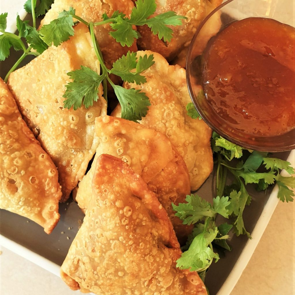 A plate of samosas with beef, pea and potato filling.