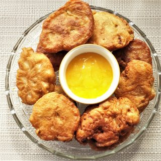 A plate of banana fritters surrounding a bowl of lemon caramel dipping sauce.