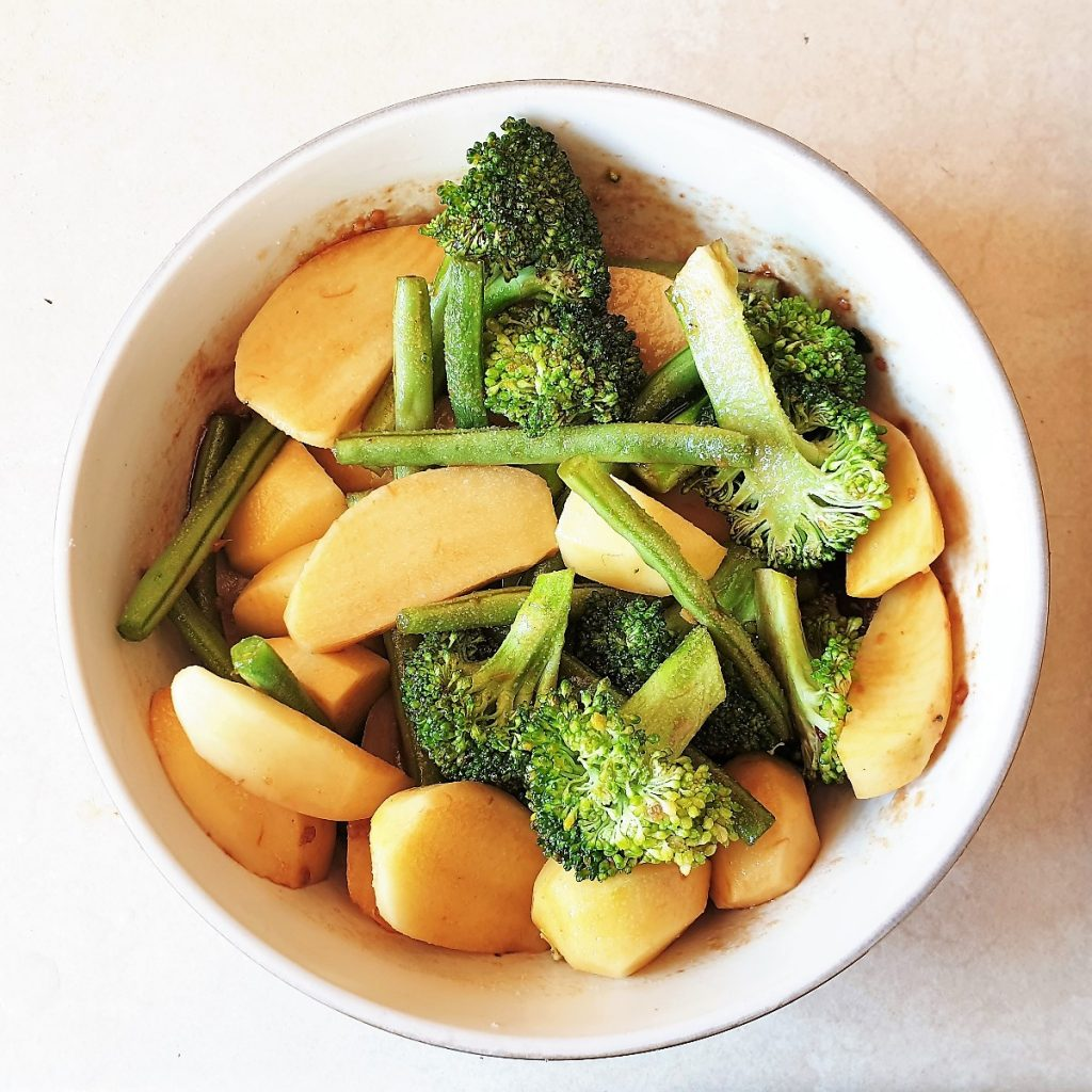 A bowl o potatoes, broccoli and green beans mixed with honey garlic marinade.