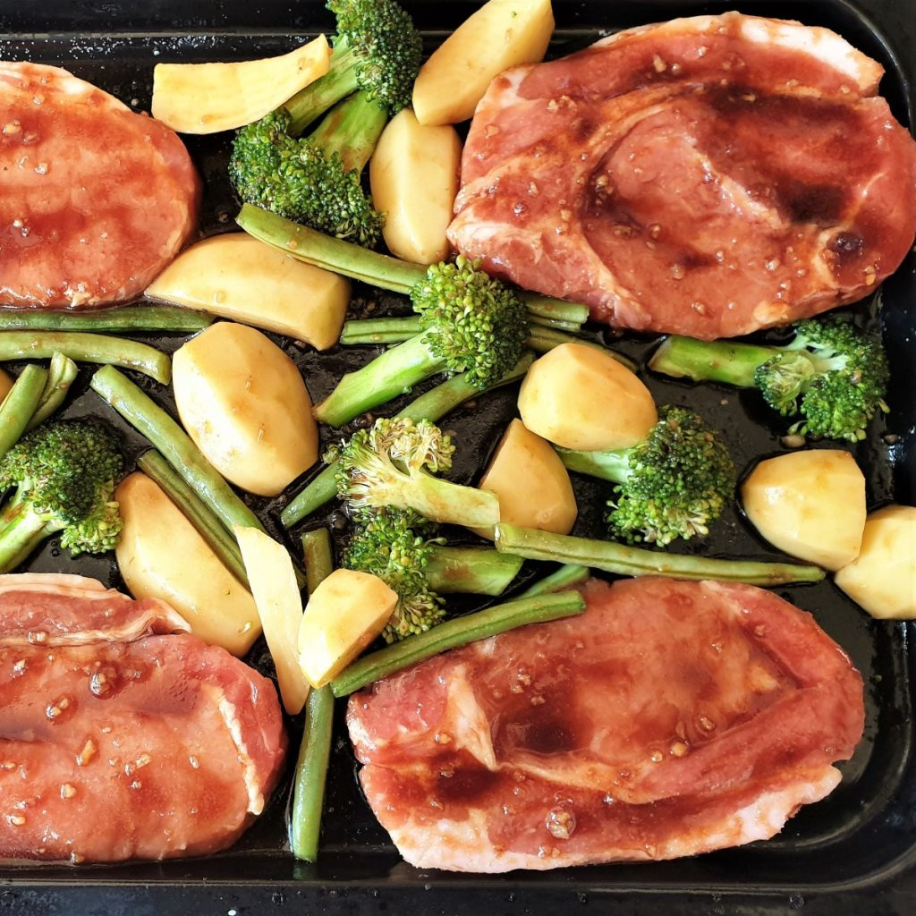 Pork chops on a baking sheet with vegetables.