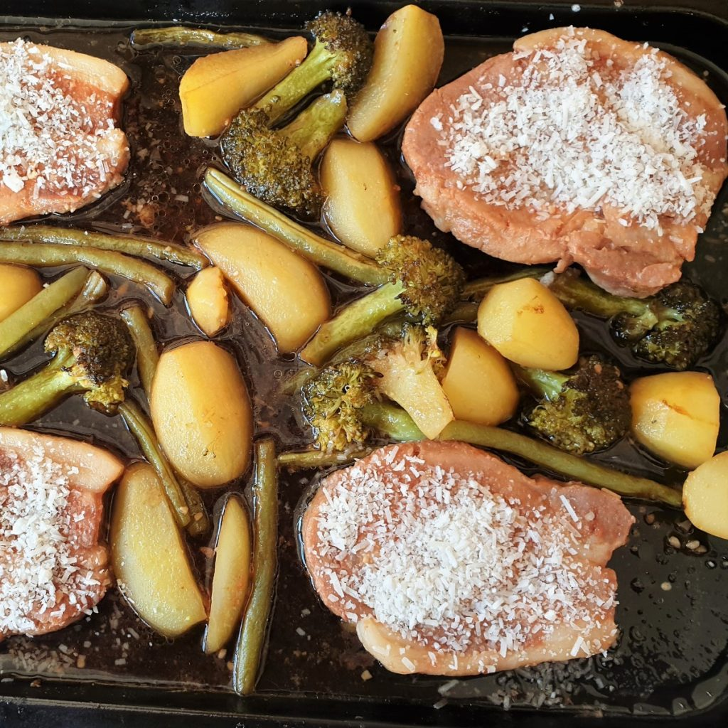 Sheet pan pork chops with potatoes, broccoli and green beans sprinkled with parmesan.