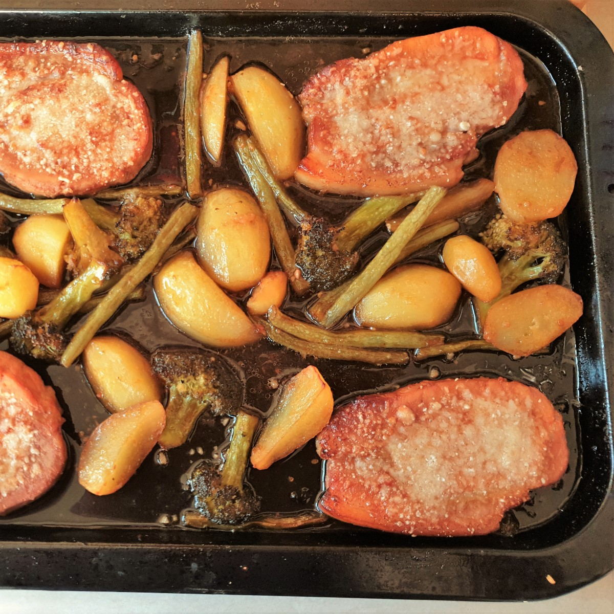Sheet pan port chops with potatoes, broccoli and green beans sprinkled with parmesan.