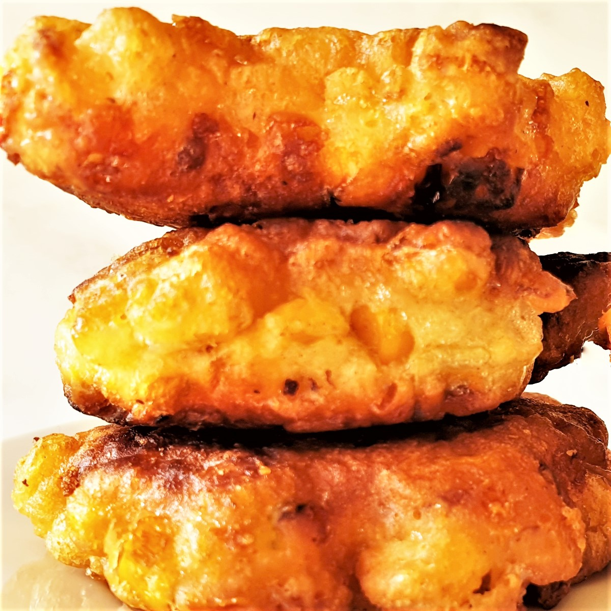 A pile of three fried crispy sweetcorn fritters.