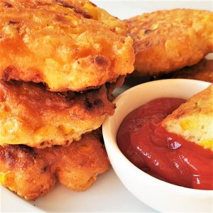 A pile of three fried crispy sweetcorn fritters with a dipping sauce.