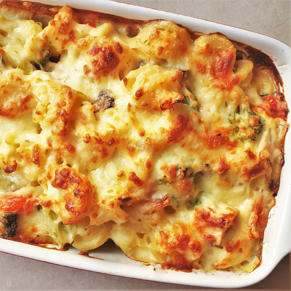 A dish of cheesy chicken and vegetable pasta bake covered with melted cheese