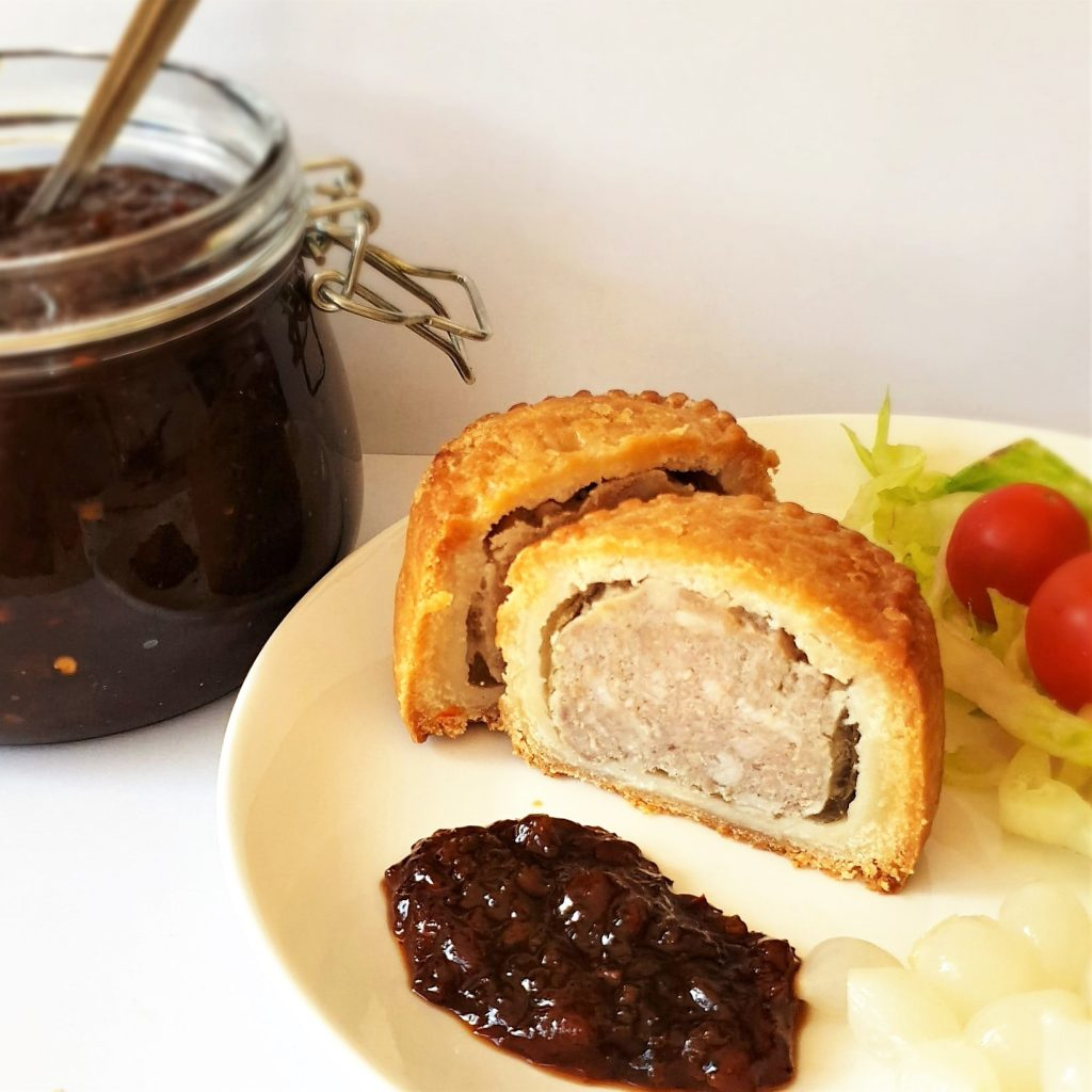 A spoonful of Mrs Balls chutney on a plate with a pork pie