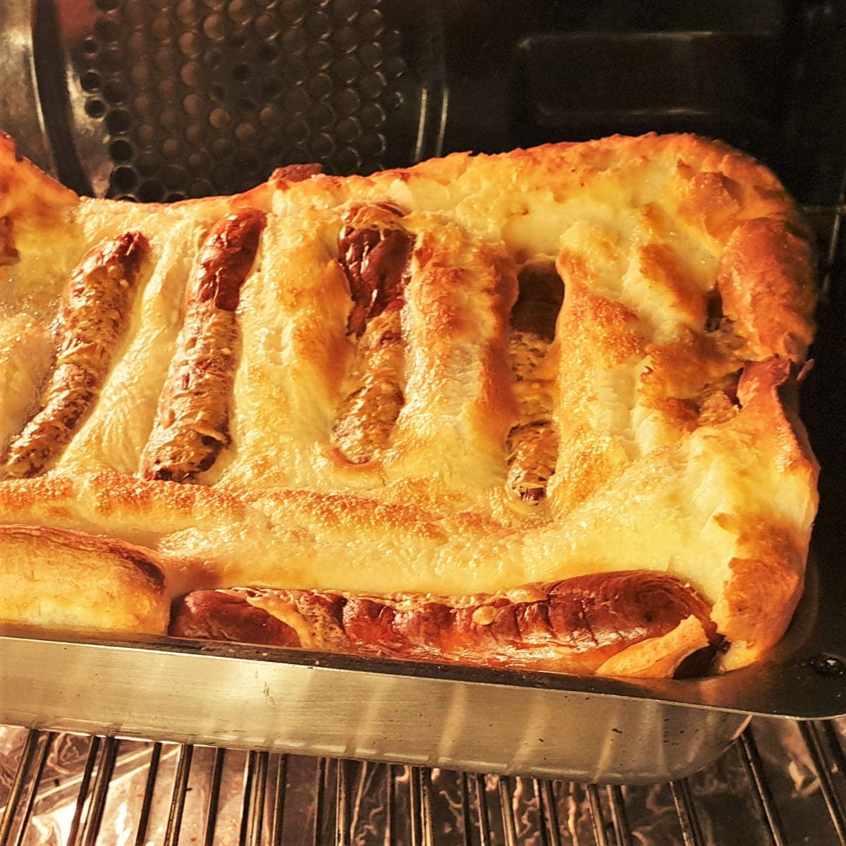 A tray of toad in the hole showing the sausages covered in wll-risen batter