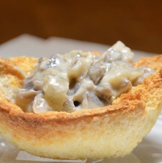 A single breadcup filled with creamed mushrooms on a plate.