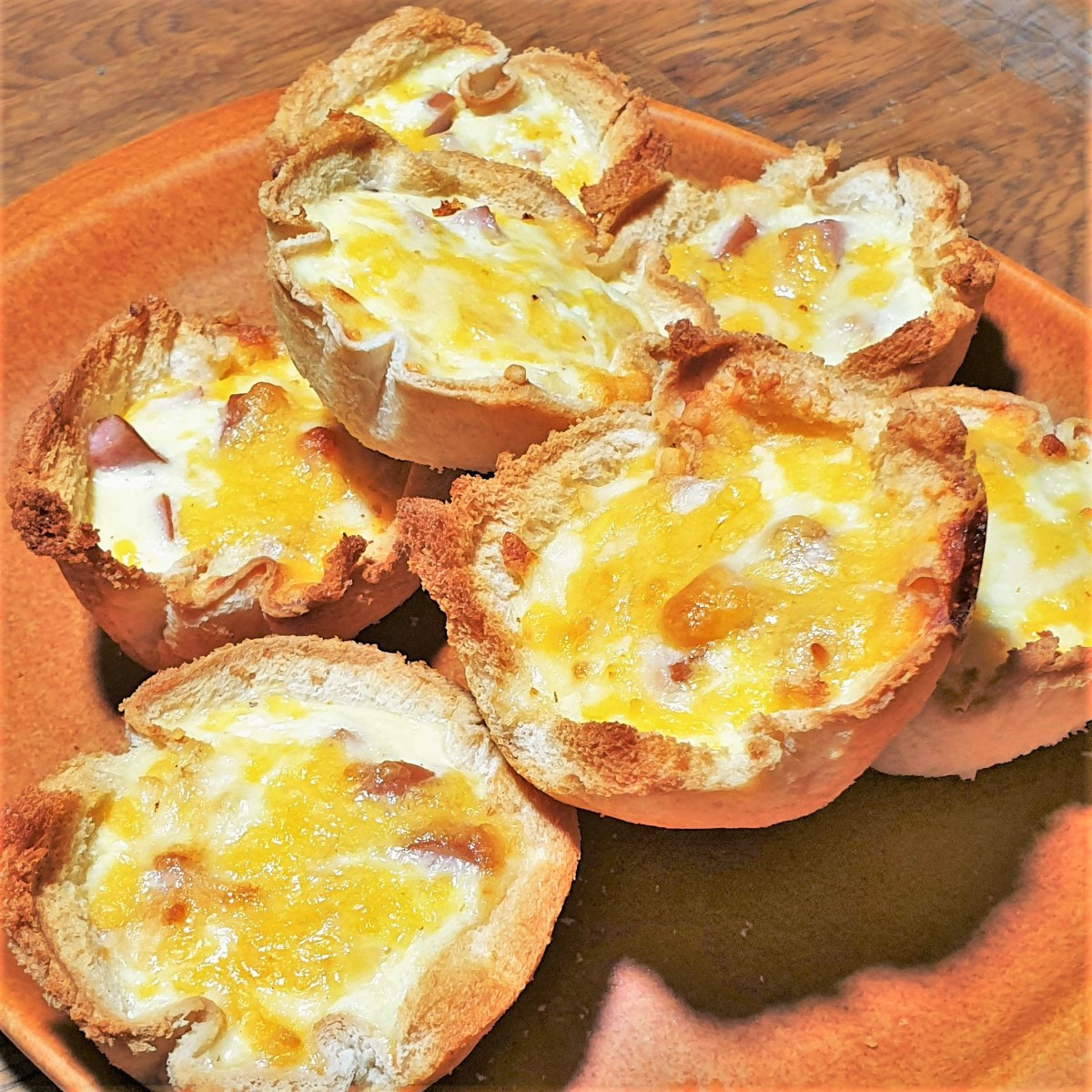 A plate of breadcups filled with egg and chopped sausage.