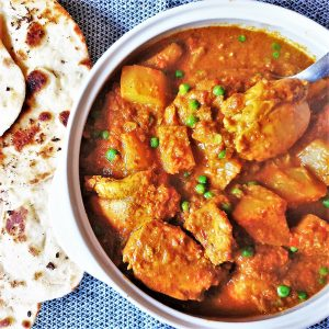 A dish of chicken bhuna with naan bread.