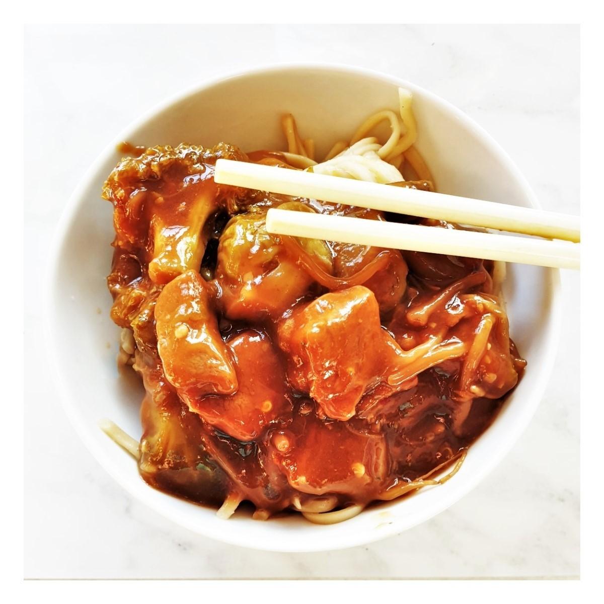A bowl of roast pork in garlic sauce with chopsticks.