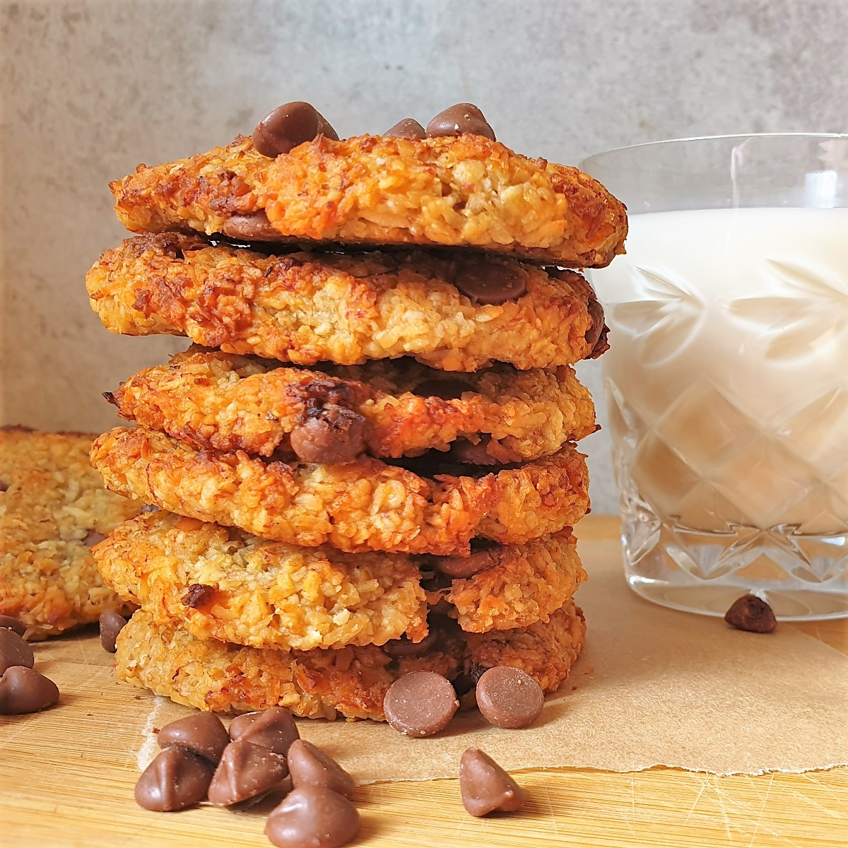 A pile of banana oat cookies with a glass of milk.