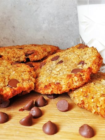 Banana oat cookies next to a glass of milk.