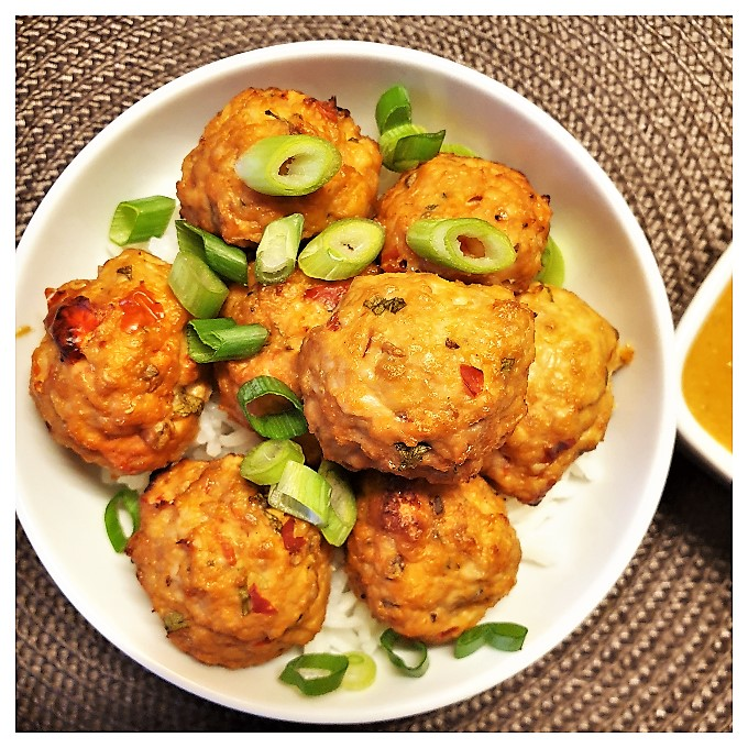 A dish of Thai meatballs sprinkled with chopped spring onions.