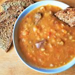 A dish of beef vegetable soup with a slice of bread.