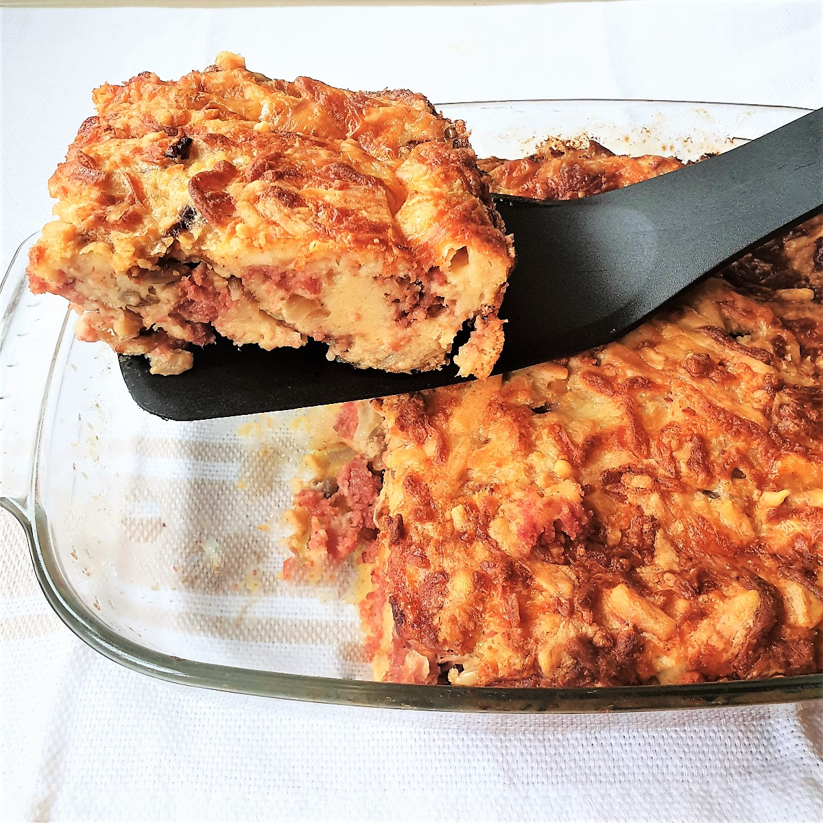 A slice of bully beef quiche being lifted from the baking dish.