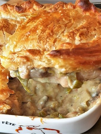 A spoonful of chicken, leek and mushroom pie being lifted from the baking dish.