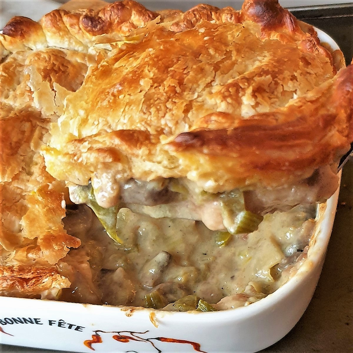"""A slice of chicken leek and mushroom pie being lifted from a dish."