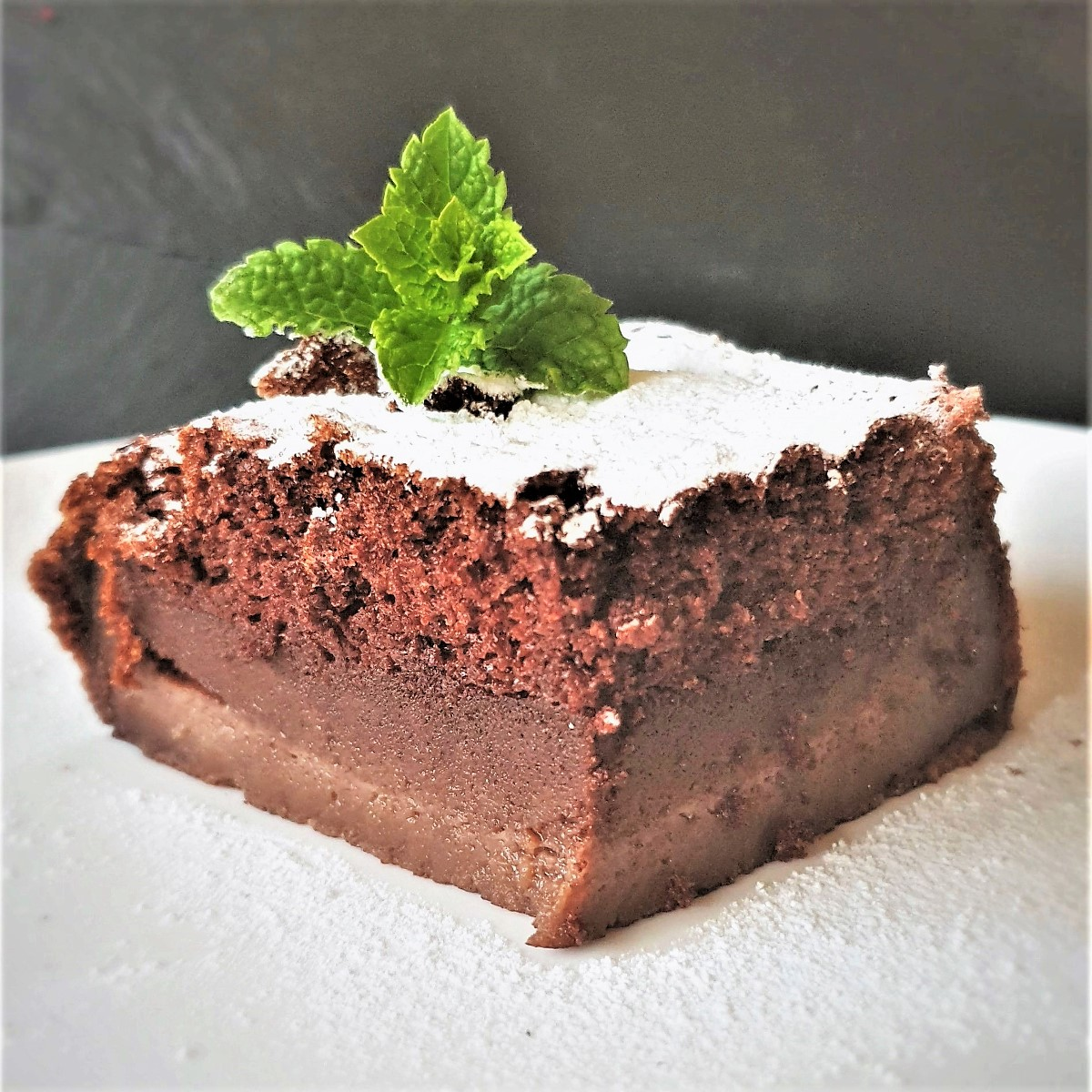 A slice of chocolate magic cake on a plate, clearly showing the three distinct layers.