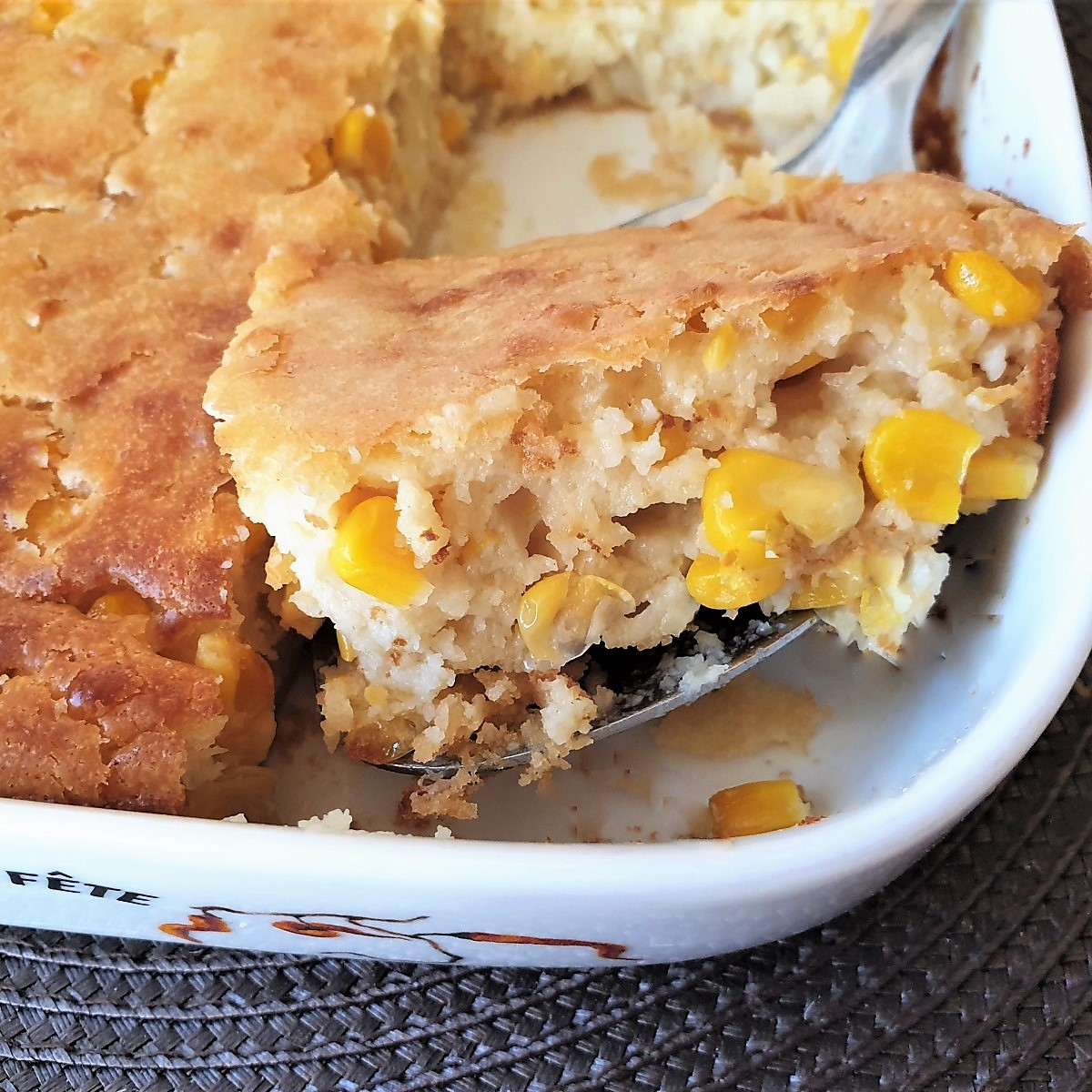 A spoonful of cornbread casserole being lifted from the baking dish.