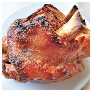 A crispy pork knuckle on a plate.