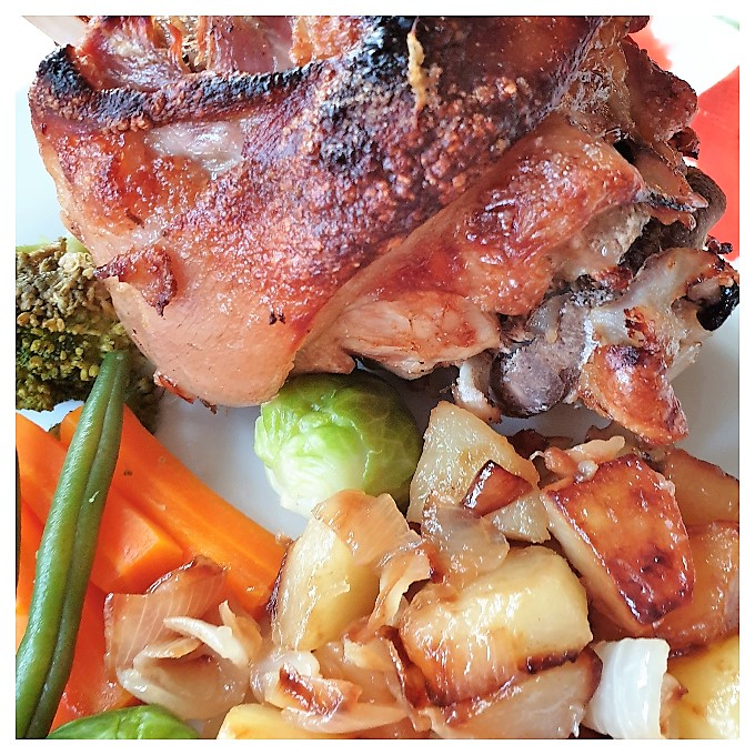 A crispy pork knuckle on a plate with vegetables and potatoes.
