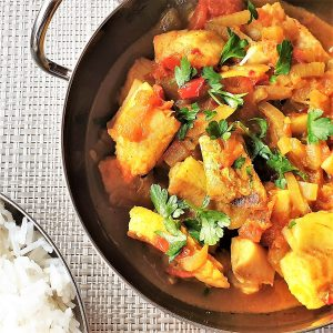Easy fish curry in a bowl next to a bowl of rice.