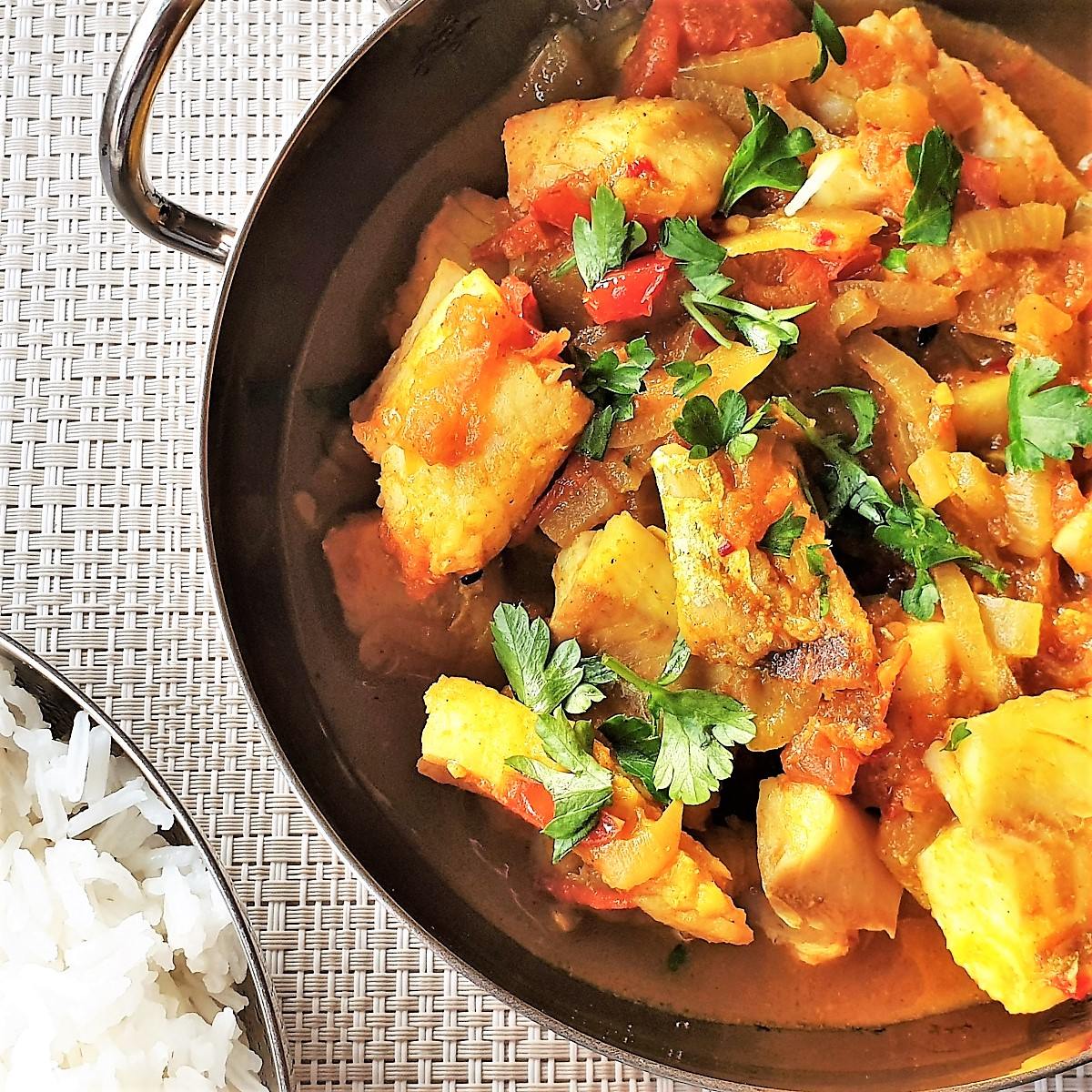 Fish curry in a balti dish next to a dish of white rice.