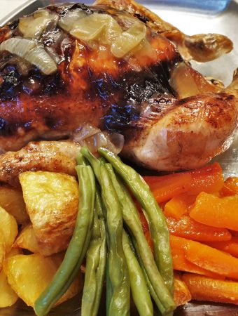 A honey lemon roast chicken on a plate with vegetables.