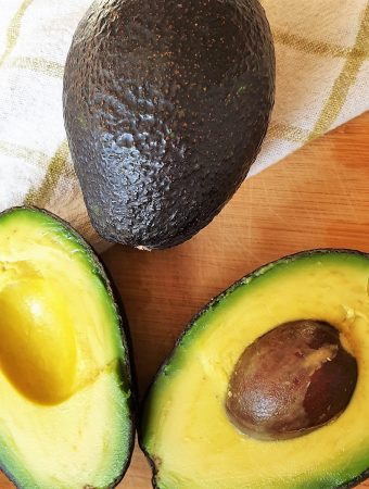 Two avocados - one whole one and the other cut in half.