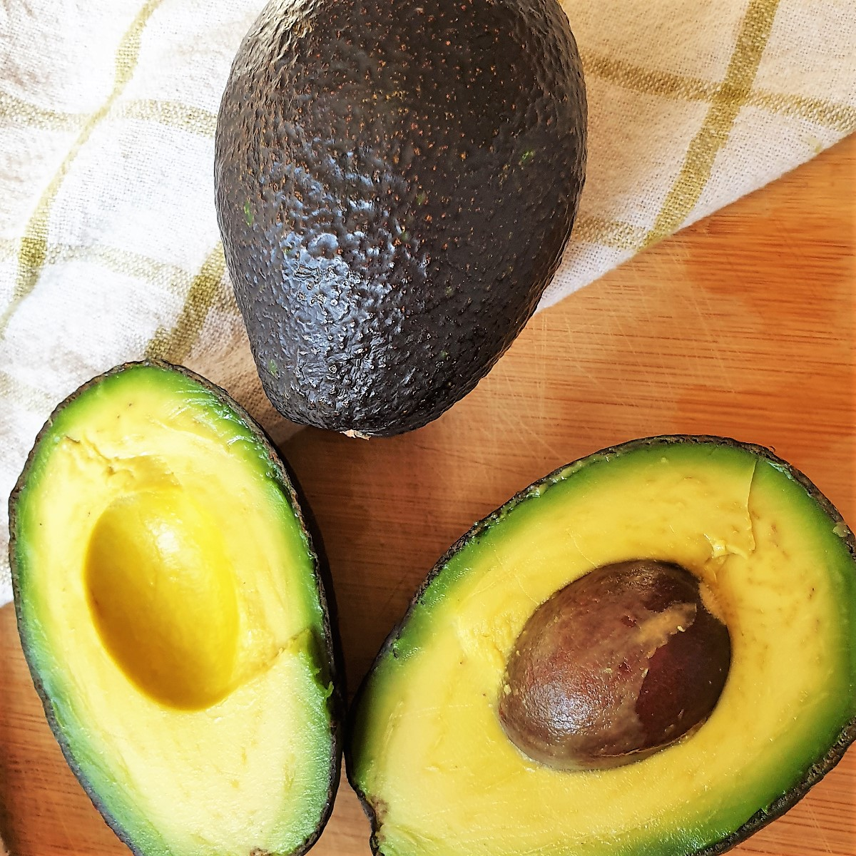 Two avocados - one whole one and one cut in half.