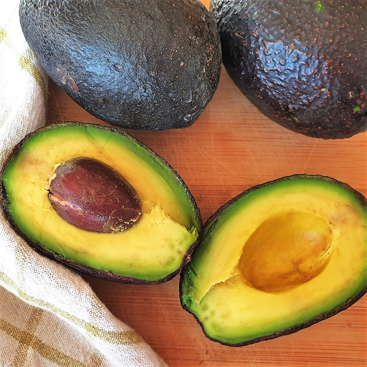 Three avocados - two whole one and one cut in half.