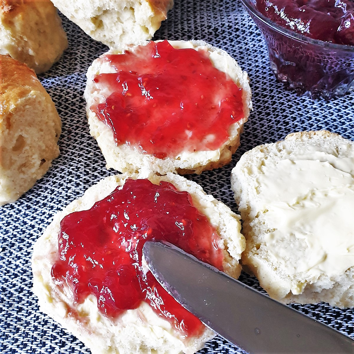 A scone being spread with jam.