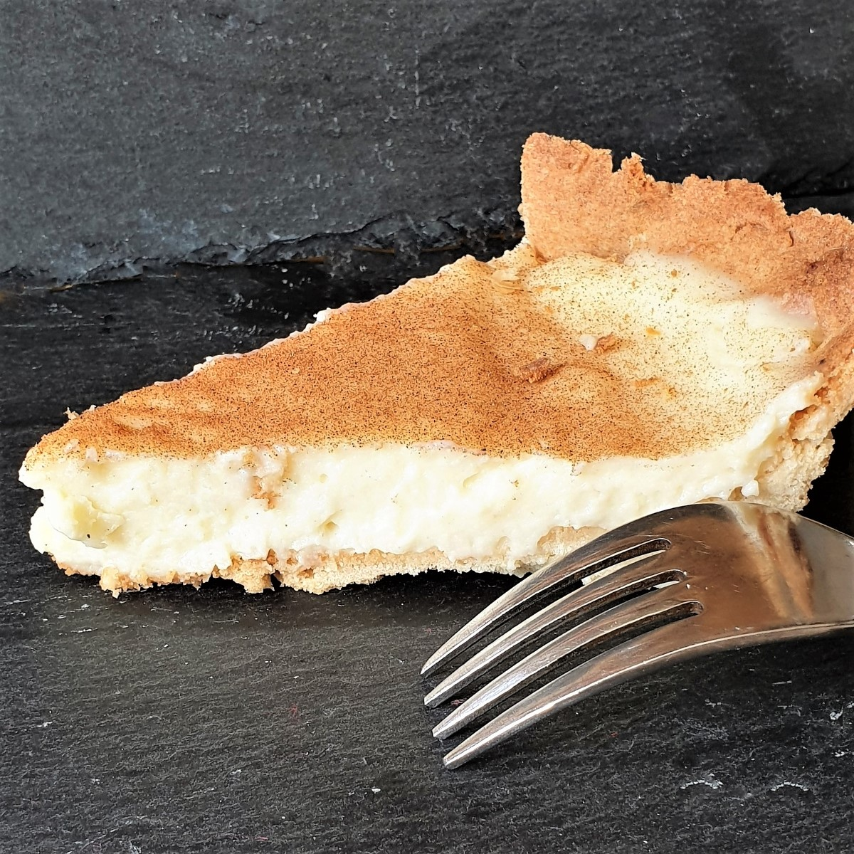 A slice of milk tart next to a fork, showing the set filling.